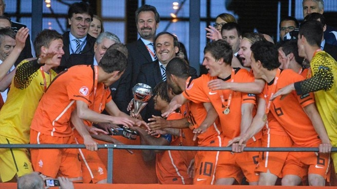UEFA President Michel Platini presents the trophy